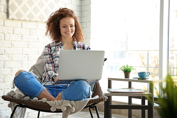 Young woman sitting at home on her laptop