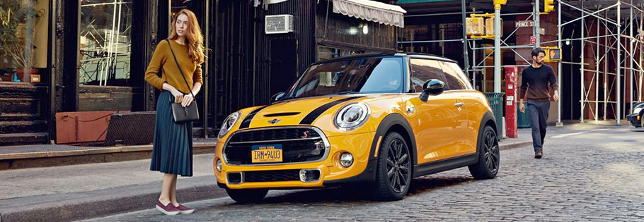 yellow black 2018 MINI Cooper Hardtop 2 Door parked on the street with a woman in the front