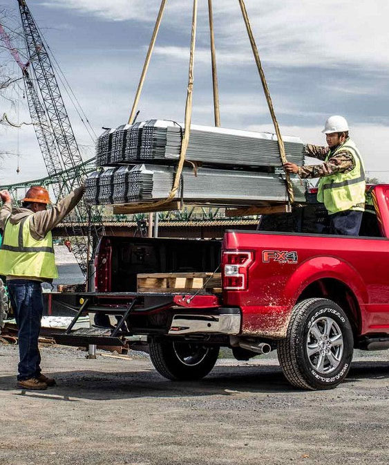 workers putting steel bars in the back of the red 2018 f-150