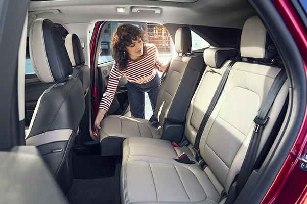 Sales associate showing the interior features of a Ford SUV