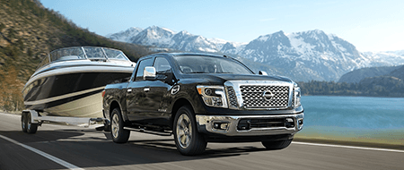 Nissan TITAN® SL highlighting towing capacity shown in Magnetic Black with optional equipment. [*]