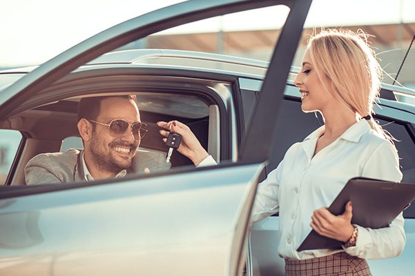 woman handing man car keys
