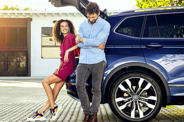A happy couple at the rear of a Tiguan in Atlantic Blue Metallic with the liftgate open.