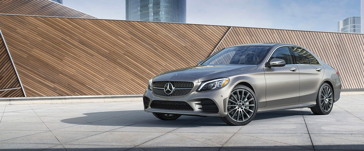2021 Mercedes-Benz C-Class in Selenite Grey parked on a sleek rooftop with views of the city skyline