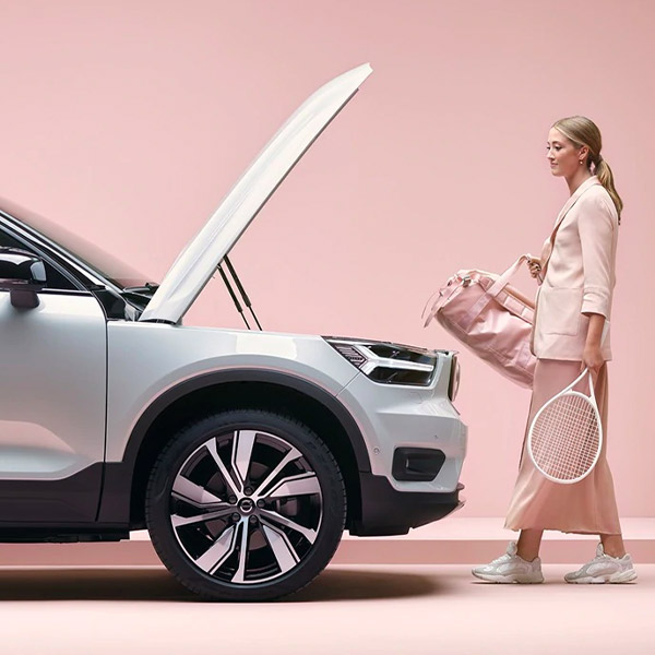 Woman using under the hood of a 2021 Volvo XC40 Recharge as storage for her tennis bag