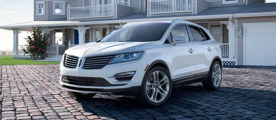 A Lincoln MKC shown in Ingot Silver is seen parked on a paver stone drive way.
