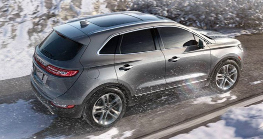 A Lincoln MKC is seen being driven along a snowy hilltop road.
