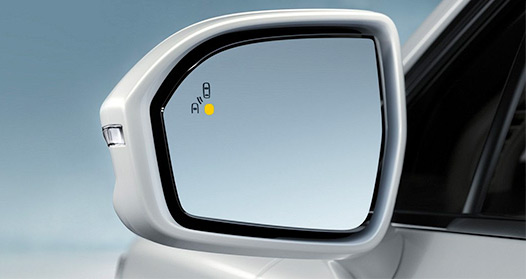 The side mirror of a Lincoln MKC with the available blind spot indicator illuminated.